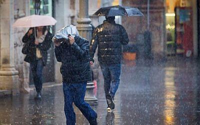 People walk in the rain on Jaffa street in downtown Jerusalem on December 1, 2016. (Yonatan Sindel/Flash90)