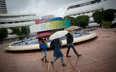 Israelis walk in the rain on Dizengoff Street in Tel Aviv on December 2, 2016 (Miriam Alster/Flash90)