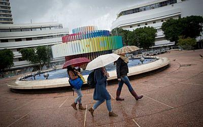 Israelis walk in the rain on Dizengoff Street in Tel Aviv on December 2, 2016 (Miriam Alster/Flash90)