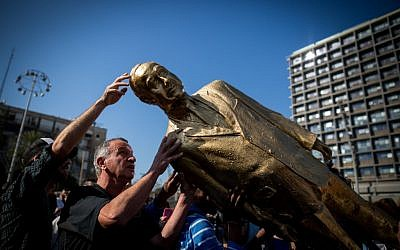 A golden statue of Prime Minister Benjamin Netanyahu is toppled in Rabin Square in Tel Aviv on December 6, 2016, hours after it was placed overnight by artist Itay Zalait, without permission from the Tel Aviv municipality. (Miriam Alster/Flash90)