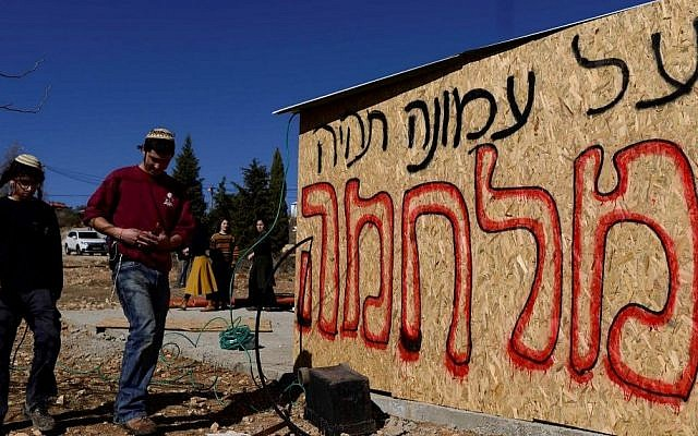 "Jewish youth prepare places for people to sleep in as they plan to resist the evacuation of Amona in the West Bank, on December 9, 2016. The writing on the structure reads ""there will be a war for Amona."" (Tomer Neuberg/Flash90)"