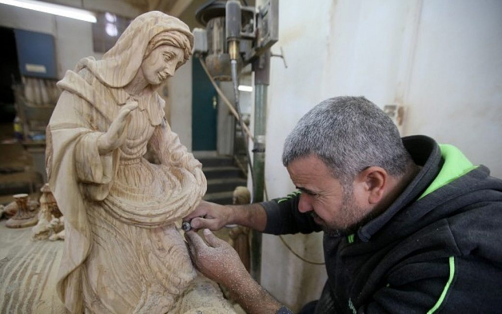 A Palestinian carpenter carves a wooden sculpture at a workshop in Bethlehem, on December 13, 2016. Promoting Bethlehem's famous olive wood carvings may be the type of tourism that can revive the city's struggling economy. (Wisam Hashlamoun/Flash90)