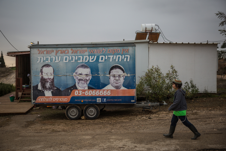 A young Jewish boy walks past an old sigh advertising extreme right-wing activists Itamar Ben Gvir, Baruch Marzel, and Michael Ben-Ari, in the Jewish settlement of Amona in the West Bank, on December 16, 2016.(Hadas Parush/Flash90)