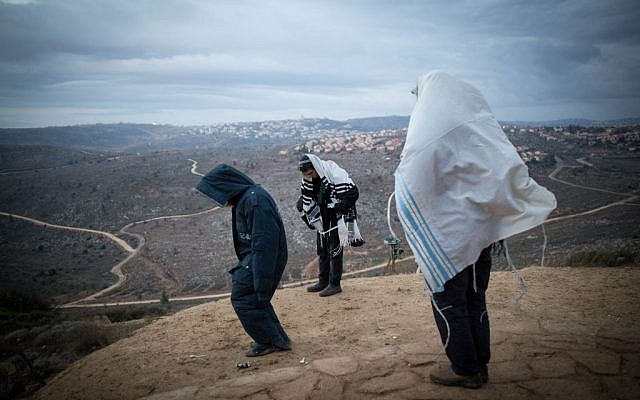 Jewish men pray early in the morning on the hill overlooking Ofra in the Jewish outpost of Amona in the West Bank, on December 18, 2016. (Miriam Alster/Flash90