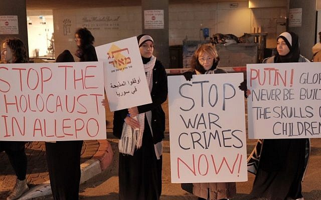 Protesters hold signs during a protest international community's failure to stop the reported massacres of civilians trapped in the besieged Syrian city of Aleppo near the Russian embassy in Tel Aviv on December 18, 2016. (Tomer Neuberg/Flash90)