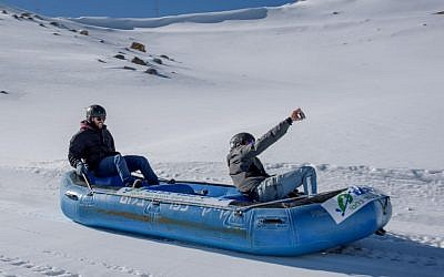 Israelis use a rubber dinghy to slide down a slope at the Mount Hermon ski resort on December 20, 2016. (Basel Awidat/Flash90)