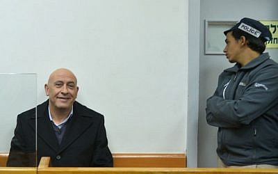 Arab Joint List member Basel Ghattas, left, is brought to court for a remand hearing after his arrest on December 22, 2016 on suspicion of smuggling cellphones to Palestinian prisoners, at the Rishon Lezion Magistrate's Court, December 23, 2016. (Avi Dishi/Flash90)