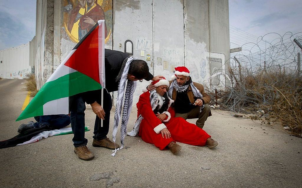 Palestinian protesters dressed as Santa Claus during a demonstration against Israel's  security wall in Bethlehem, on December 23, 2016. (Wisam Hashlamoun/FLASH90)