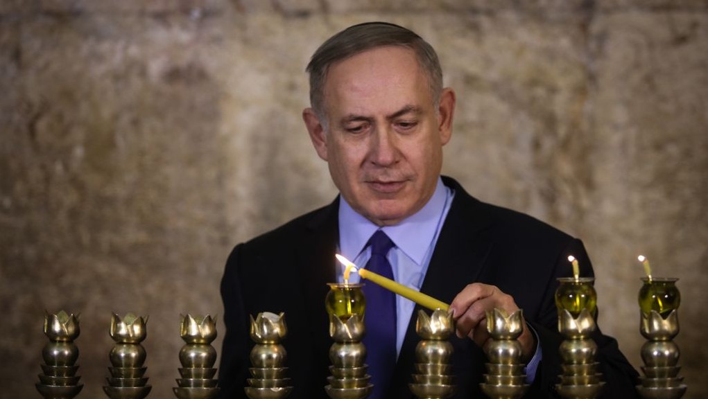 Israeli Prime Minister Benjamin Netanyahu lights the Hanukkah candles on the First night of the Jewish holiday at the Western Wall in Jerusalem Old City on December 25, 2016. (Marc Israel Sellem/POOL)