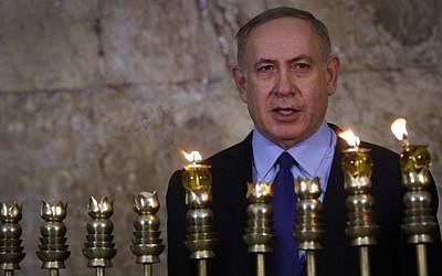 Prime Minister Benjamin Netanyahu lights Hanukkah candles at the Western Wall in Jerusalem's Old City on December 25, 2016. (Marc Israel Sellem/POOL)