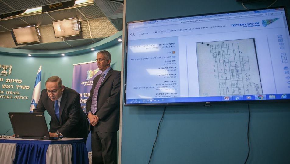 "Prime Minister Benjamin Netanyahu during a press conference inaugurating the State archive on the ""Yemenite Children Affair,"" now open to the public online, at the Prime Minister's Office in Jerusalem on December 28, 2016. Alongside him is state archivist Yaakov Lozowick. Families from Yemenite and North African Jewish communities maintain the Israeli government systematically kidnapped their children from Israeli hospitals and put them up for adoption during the immigration wave in the 1950s. (Ohad Zwigenberg/POOL)"