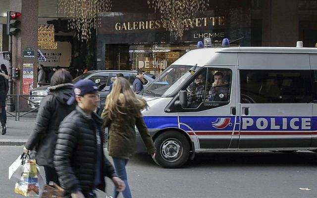 A police van is parked outside the Galeries Lafayette department store in Paris, France, Tuesday, Dec. 20, 2016, the day after a truck ran into a crowded Christmas market, killing 12 people Monday evening in Berlin, Germany. (AP Photo/Thomas Padilla)