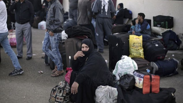 A Palestinian woman sits next to her luggage as she waits to cross to the Egyptian side of the Rafah border crossing, in Rafah, Gaza Strip, October 19, 2016. (AP Photo/Adel Hana, File)