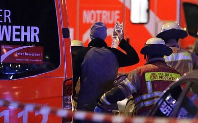 Firefighters attend an injured person after a truck ran into crowded Christmas market in Berlin, Germany, Monday, Dec. 19, 2016. (AP Photo/Michael Sohn)