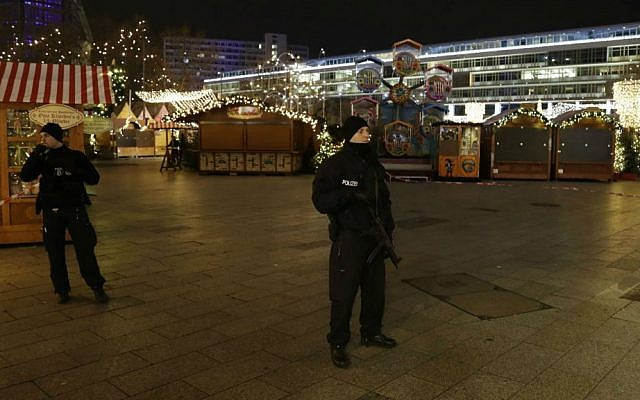 Police guard a Christmas market after a truck ran into crowds at the site in Berlin, Germany, Monday, Dec. 19, 2016. (AP Photo/Michael Sohn)