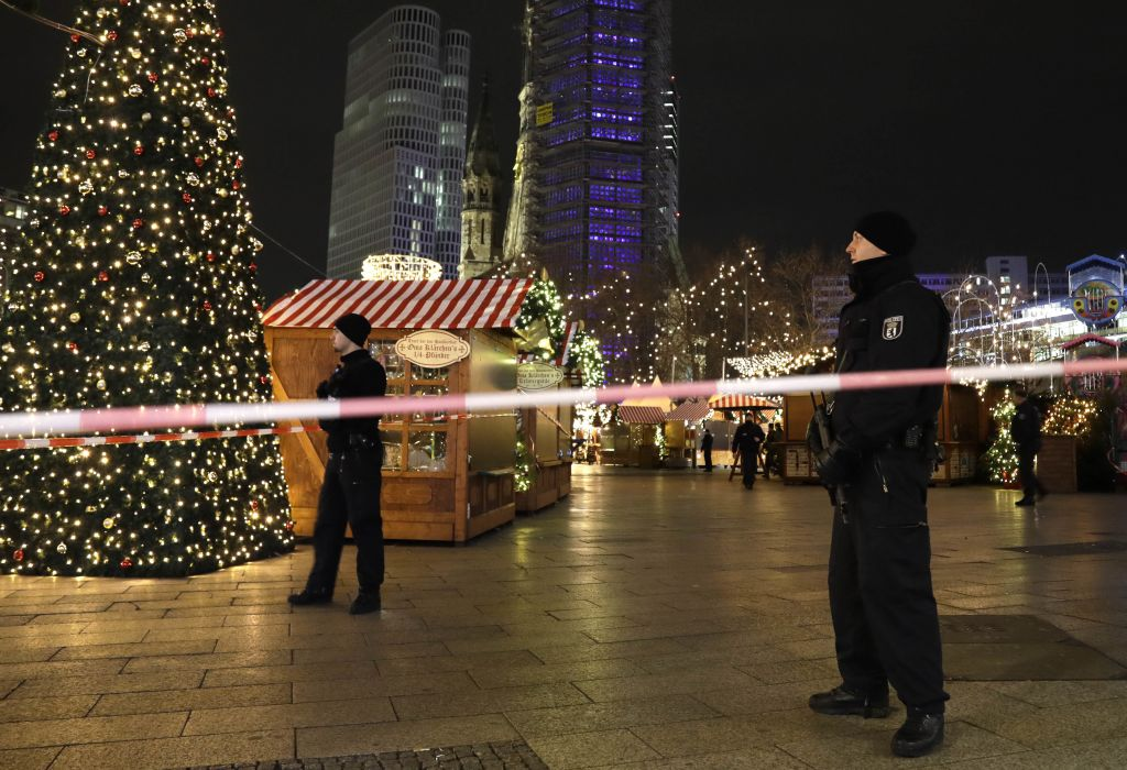 Firefighters look at a toppled Christmas tree after a truck ran into a crowded Christmas market and killed several people in Berlin, Germany, Monday, Dec. 19, 2016. (AP Photo/Michael Sohn)