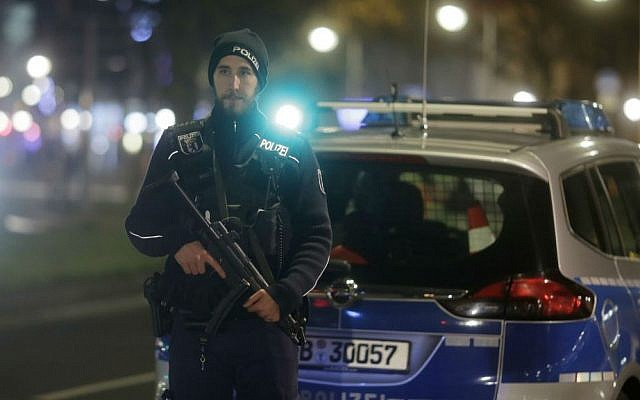 A police officer with a submachine gun stands guard after a truck ran into a crowded Christmas market in Berlin, Germany, Monday, Dec. 19, 2016. (AP Photo/Markus Schreiber)