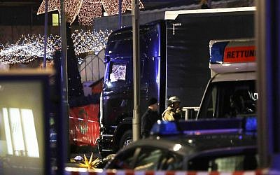 Police stand beside a damaged truck which ran into crowded Christmas market in Berlin, Germany, Monday, Dec. 19, 2016. (AP Photo/Michael Sohn)