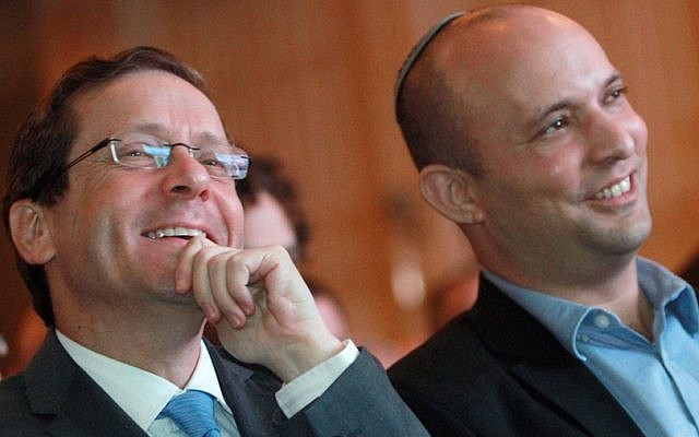 Zionist Union leader Isaac Herzog, left, and Jewish Home chair Naftali Bennett listen to a debate on the economy in Tel Aviv, March 11, 2015. (Gil Cohen Magen/AFP/Getty Images)