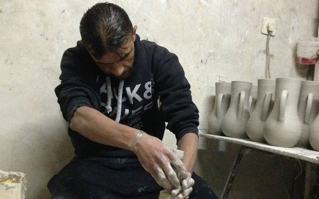 Master ceramic artisan Bilal Saleima at work in his tiny workshop in Halhul, next to Hebron. He says he can spin 100 coffee or espresso mugs a day. (Brett Kline/Times of Israel)