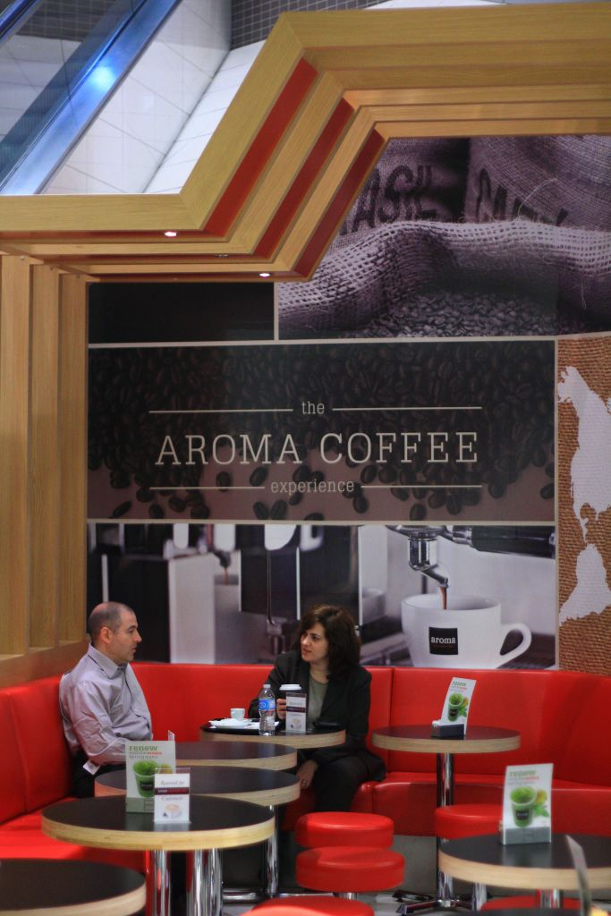 Customers sit below an Aroma sign in a Toronto location. (Courtesy)