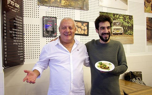 Matan Abrahams, who is the head chef at the Hudson Brasserie, a high-end Steakhouse in Tel Aviv, stands with Issa Maron on November 30, 2016, holding their shared creation of the first-ever hummus and slow-cooked barbecued mix. (Dov Lieber / Times of Israel)