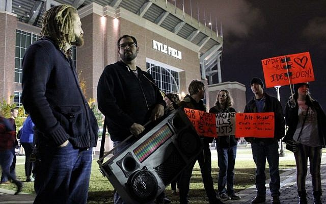 A man holding a large boombox blasts Dr. Martin Luther King's 'I have a dream' at a demonstration at Texas A&M University against Richard Spencer, December 6, 2016. (Ricky Ben-David/Times of Israel)