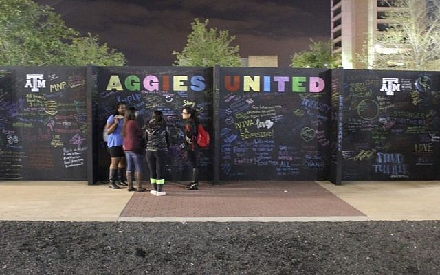 Students write messages of unity on a protest wall at Texas A&M University where hundreds were protesting a speech given by a self-styled leader of the so-called alt-right movement.  (Ricky Ben-David/Times of Israel)