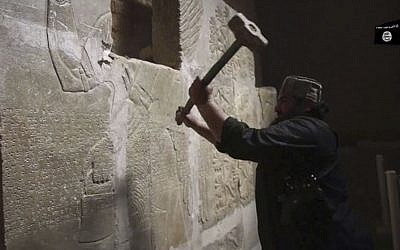 This image made from video posted online by Islamic State in April 2015 shows a man taking a sledgehammer to a stone carving at the ancient site of Nimrud near Mosul, Iraq. (Militant video via AP)
