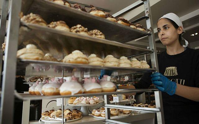 In this Thursday, Dec. 15, 2016 photo, a bakery employee wheels sufganiyot, or Hanukkah doughnuts in Bnei Brak, Israel. (AP Photo/Dan Balilty)