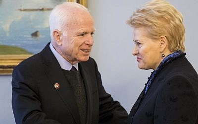 Lithuania's President Dalia Grybauskaite, right, welcomes US Senator John McCain, R-Ariz. during a welcome ceremony in the Presidential palace in Vilnius, Lithuania, Thursday, Dec. 29, 2016. (AP Photo/Mindaugas Kulbis)