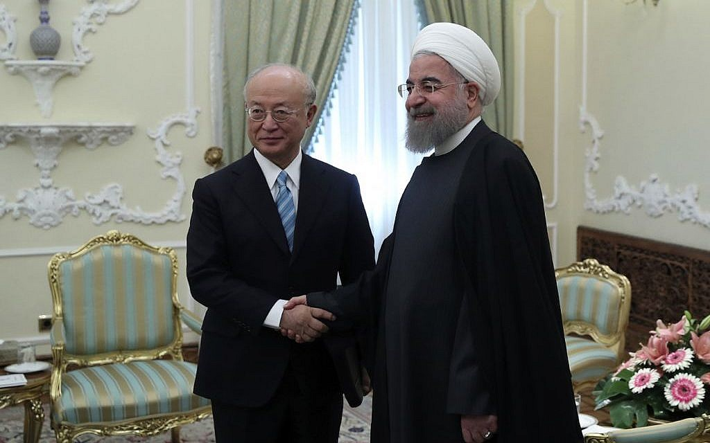 President Hassan Rouhani (r) and Director General of the International Atomic Energy Agency, IAEA, Yukiya Amano shake hands ahead of their meeting at the Presidency office in Tehran, Iran, on December 18, 2016. (Iranian Presidency Office/AP)