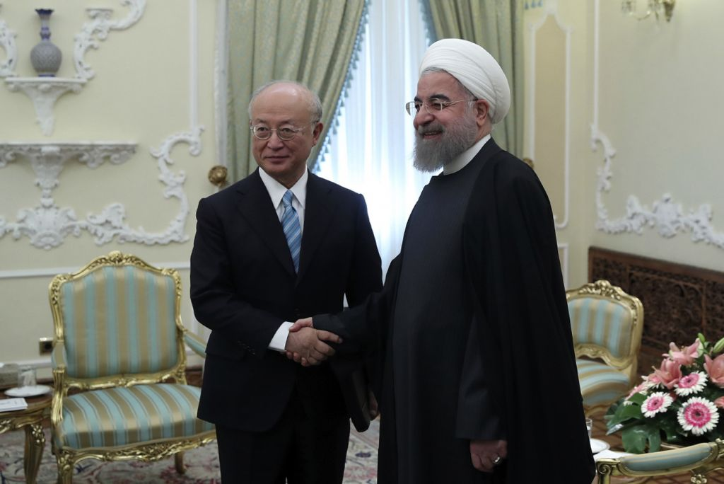 In this photo released by official website of the office of the Iranian Presidency, President Hassan Rouhani, right, and Director General of the International Atomic Energy Agency, IAEA, Yukiya Amano shake hands for media at the start of their meeting at the Presidency office in Tehran, Iran, Sunday, December 18, 2016. (Iranian Presidency Office/AP)