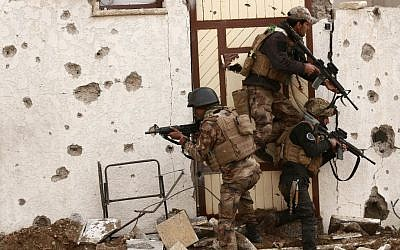 Soldiers with Iraq's elite counter terrorism forces secure houses and streets during fighting against Islamic State militants to regain control of the eastern neighborhoods of Mosul, Iraq, Tuesday, December 13, 2016. (AP Photo/Hadi Mizban)