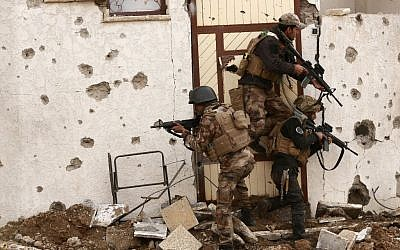 Soldiers with Iraq's elite counter-terrorism forces secure houses and streets during fighting against Islamic State militants to regain control of the eastern neighborhoods of Mosul, Iraq, Tuesday, Dec. 13, 2016. (AP Photo/Hadi Mizban)