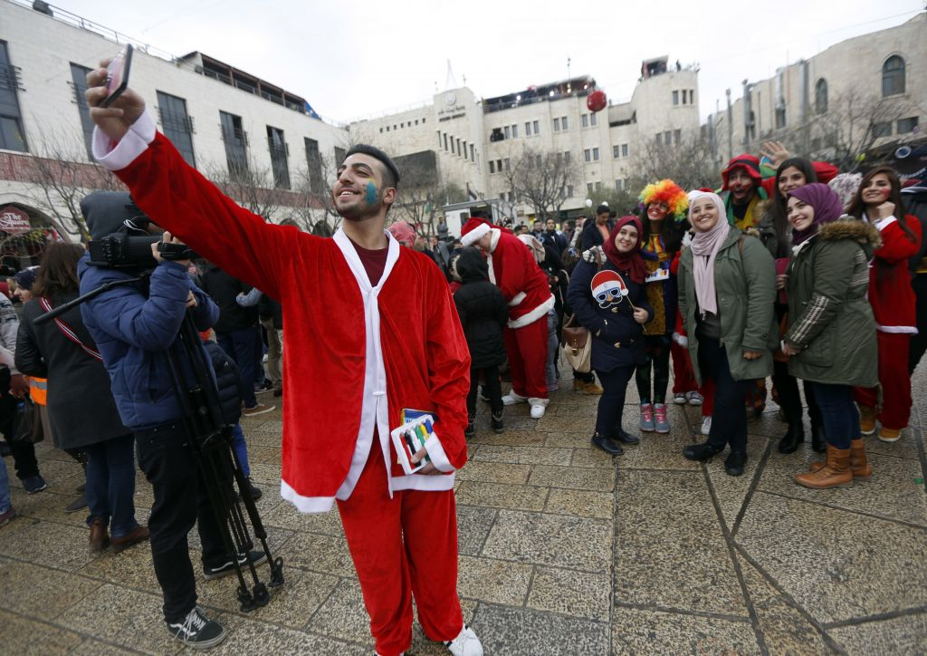 A Palestinian dressed as Santa Claus takes a picture on Christmas Eve in Manger Square, outside the Church of the Nativity, built atop the site where Christians believe Jesus Christ was born, in the West Bank City of Bethlehem, Saturday, Dec. 24, 2016 (AP Photo/Majdi Mohammed)