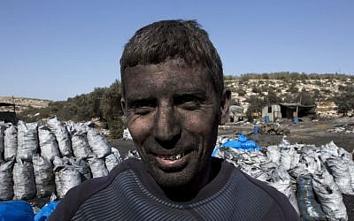 In this photo taken Monday, Nov. 21, 2016, Palestinian laborer Sami Abu Baker, 35, who has a fifteen years service in the charcoal factories, poses for a picture during a day work, in the West Bank town of Yabad, near Jenin. (Nasser Nasser/AP)