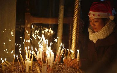 A Christian worshipper lights a candle at the Church of the Nativity, built atop the site where Christians believe Jesus Christ was born, on Christmas Eve, in the West Bank City of Bethlehem, Saturday, Dec. 24, 2016 (AP Photo/Majdi Mohammed)