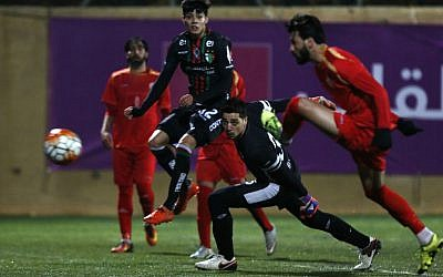 In this Thursday, Dec. 15, 2016 photo, Chile's Palestino players, in red, in action during a friendly soccer match with the Palestinian national squad in the West Bank city of Hebron. (AP Photo/Majdi Mohammed)