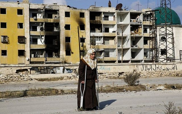 In this Sunday, December 4, 2016 photo, Nisrin Malaji returns to her looted home in the Hanano district of eastern Aleppo, Syria. (AP Photo/Hassan Ammar)