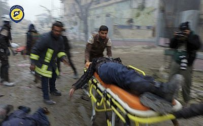 Civil Defense workers carrying a victim on a stretcher after artillery fire struck the Jub al-Quba district in Aleppo, Syria, November 30, 2016.  (Syrian Civil Defense White Helmets via AP)