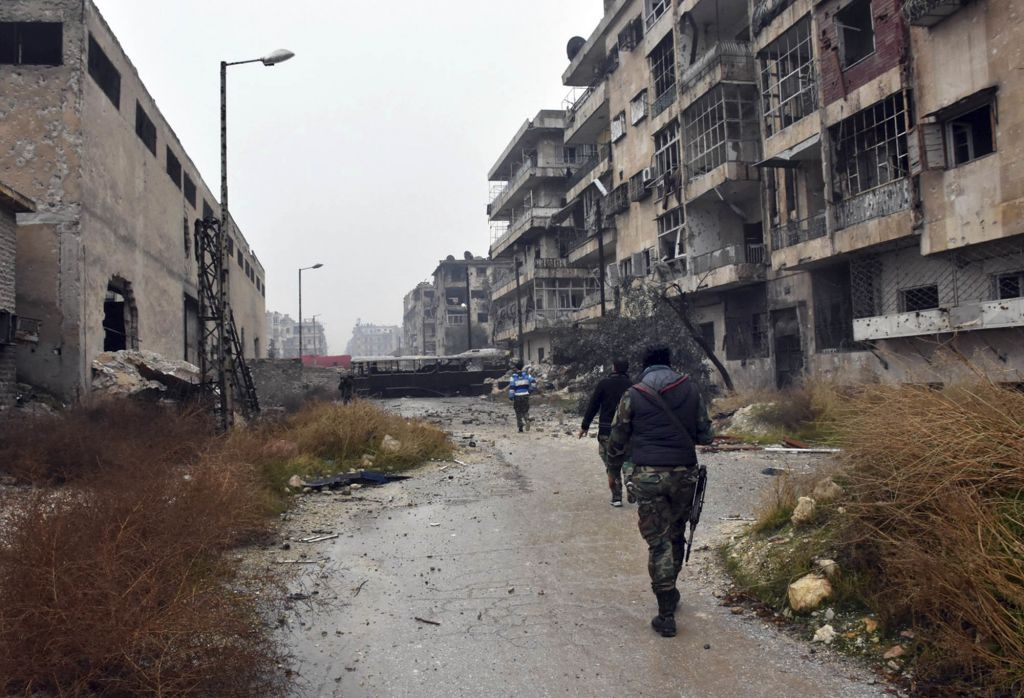 This photo released by the Syrian official news agency SANA, shows Syrian troops and pro-government gunmen marching through the streets of east Aleppo, Syria, Tuesday, Dec. 13, 2016. (SANA via AP)