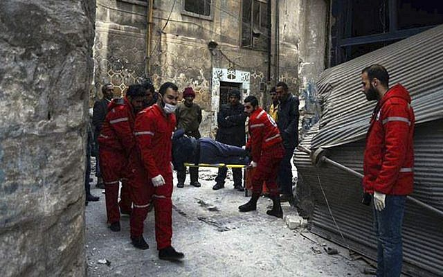 This Wednesday, Dec. 7, 2016 photo, released by the International Committee for the Red Cross, shows members of the Syrian Arab Red Crescent carrying a patient on a stretcher out of a medical facility in the Old City of Aleppo, Syria. (Syrian Arab Red Crescent/Noor Hazouri via AP)