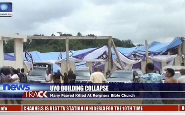 In this image taken from video people stand at the scene after the roof of The Reigners Bible Church International collapsed onto worshipers killing dozens in Uyo, southern Nigeria, December 10, 2016. (Channels TV via AP)
