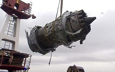 In this frame grab made available by Russian Rossiya One TV Channel on Wednesday, Dec. 28, 2016, a crane carries a fragment of a plane engine lifted by divers on a ship just outside Sochi, Russia. (Rossiya One TV Channel photo via AP)