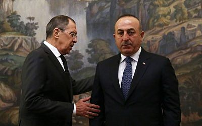 Russian Foreign Minister Sergey Lavrov, right, and Turkey's Foreign Minister Mevlut Cavusoglu attend a ceremony in memory of Russian Ambassador to Turkey Andrey Karlov, who was fatally shot by a Turkish policeman Monday at a gathering in Ankara, Turkey, before their talks on Syria in Moscow, Russia, Tuesday, Dec. 20, 2016. (Maxim Shemetov/Pool Photo via AP)