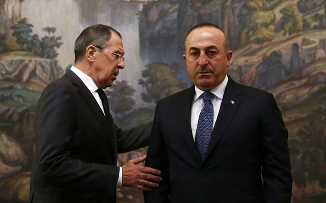 Russian Foreign Minister Sergey Lavrov, right, and Turkey's Foreign Minister Mevlut Cavusoglu attend a ceremony in memory of Russian Ambassador to Turkey Andrey Karlov, who was fatally shot by a Turkish policeman Monday at a gathering in Ankara, Turkey, before their talks on Syria in Moscow, Russia, December 20, 2016. (Maxim Shemetov/Pool Photo via AP)