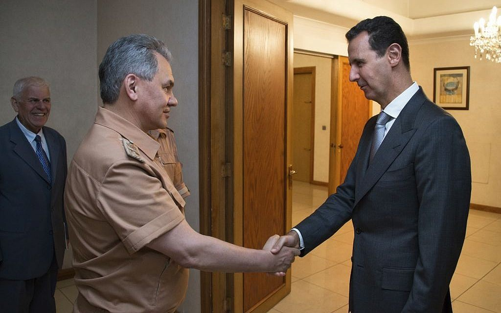 In this June 18, 2016 file photo, Syrian President Bashar Assad, right, shakes hands with Russian Defense Minister Sergei Shoigu in Damascus, Syria. (Vadim Savitsky/Russian Defense Ministry Press Service pool via AP, File)