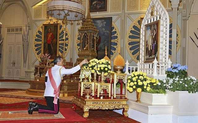 Thailand 's new king Maha Vajiralongkorn Bodindradebayavarangkun pays his respects to a portrait of the late Thai King Bhumibol Adulyadej and Thai Queen Sirikit at the Dusit Palace Thursday, December 1, 2016 in Bangkok, Thailand. (Bureau of the Royal Household via AP)