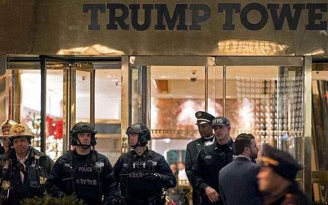 New York firefighters, police officers and others stand outside Trump Tower lobby in New York, Tuesday, Dec 27, 2016. Police hastily cleared the lobby of Trump Tower on Tuesday to investigate an unattended backpack, only to find that the bag contained children's toys. (AP/Craig Ruttle)